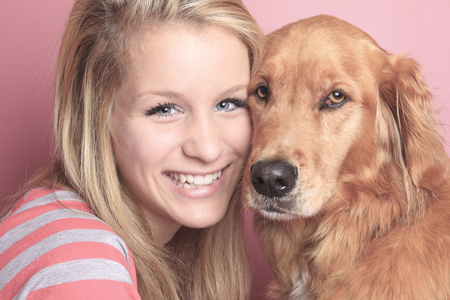 retreiver: A Girl and her dog together on a bedroom with a pink wall.