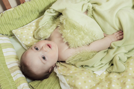 bonnie: A Overhead view of cute baby boy lying under blankets in wooden crib or cot. Stock Photo