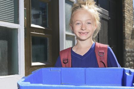 reciclar: Una chica joven con la papelera de reciclaje fuera