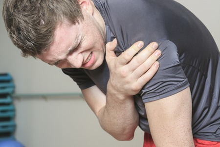 kneecap: A Portrait of a fitness man reaching for his knee in pain