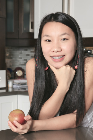 A smiling teenager girl with apple in kitchen Stok Fotoğraf