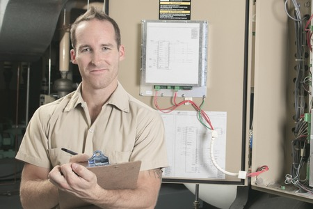 cooling: A Air Conditioner Repair Man at work Stock Photo