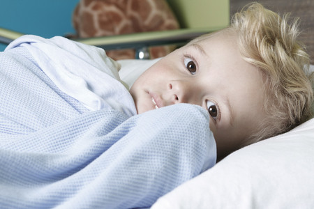 A sick little boy in a hospital bed Stock Photo