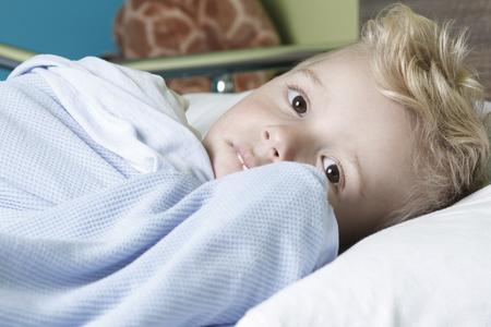 Een zieke jongetje in een ziekenhuis bed Stockfoto