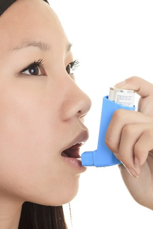 A Close up image of a young woman using inhaler.