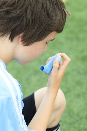 inhalator: A young soccer player taking his asthma inhalator