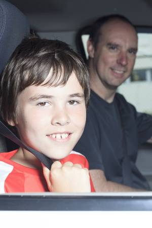 A Portrait of smiling boy in the car of his father