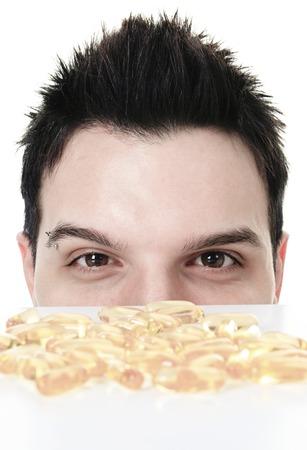 그의 눈 앞에서 오메가 -3 알약을 먹은 젊은 남자