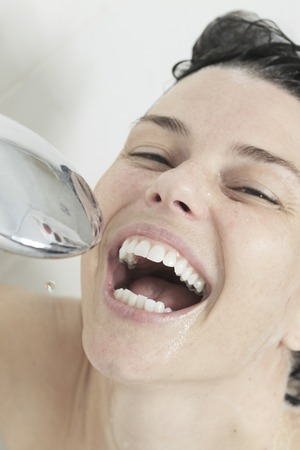 signer: A Happy signer woman showering in bathroom. Stock Photo