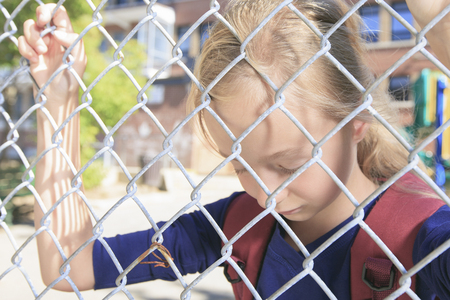 depress: sad little girl at school playground with fence on front of is face. Stock Photo