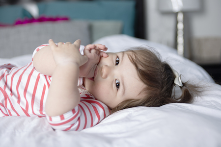 insides: A one year old girl in bed having fun