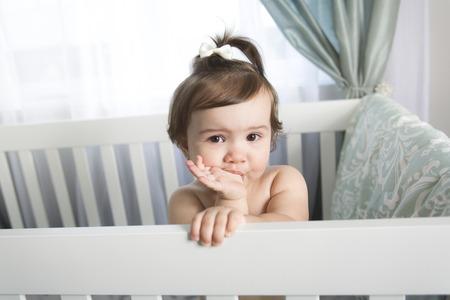 그의 작은 아기 침대에서 쉬고 놀고있는 유아 아기