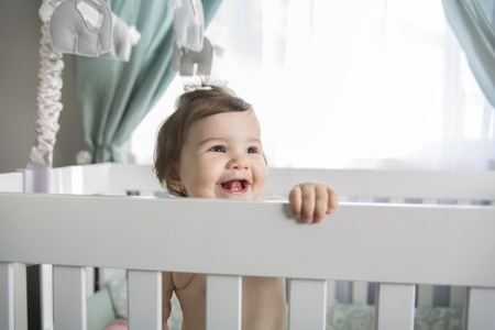 babygirl: An Infant baby resting and playing in his little baby bed Stock Photo