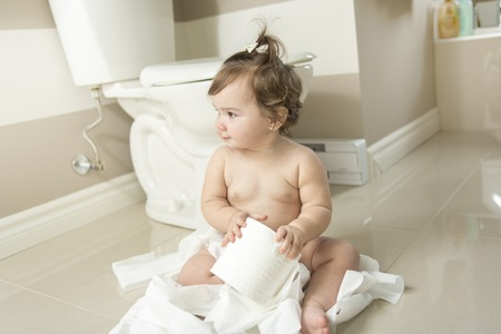 misbehavior: A Toddler ripping up toilet paper in bathroom Stock Photo