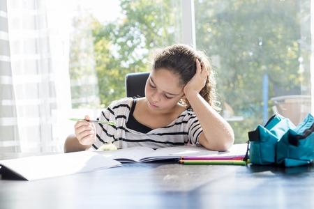 colegiala: Una colegiala estudiando con libros sobre la mesa de la cocina