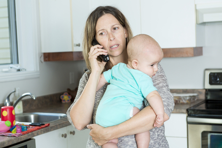help: A woman on the phone while holding her baby in her arms in the kitchen