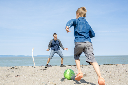 baby boys: A father play with is son on the side of the beach Stock Photo