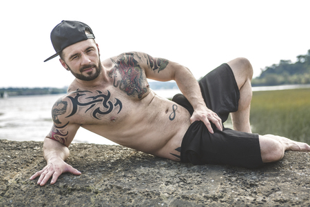 cool guy: A sexy man with tattoo outside taking good time