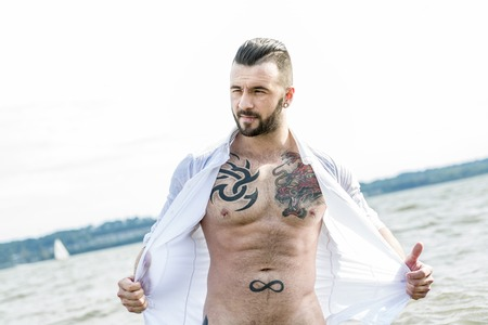 male model torso: A sexy man with tattoo outside taking good time