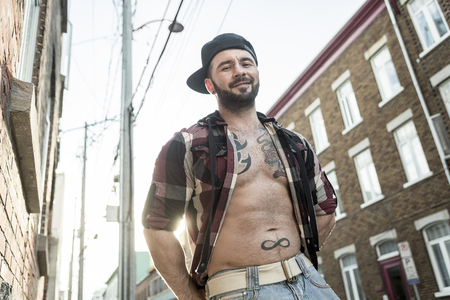 nudist young: A sexy man with tattoo outside in a city street