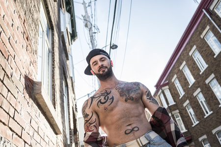 A sexy man with tattoo outside in a city street