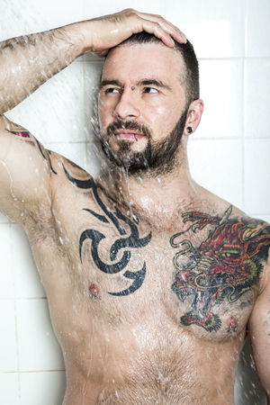 metrosexual: A sexy man with tattoo  on the shower
