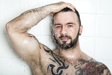 nudist young: A sexy man with tattoo  on the shower