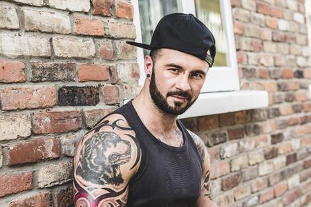 Een sexy man met tatoeage buiten in een stad straat