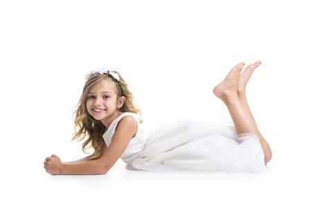 Een klein meisje draagt een witte jurk op studio