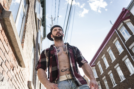 nudist: A sexy man with tattoo outside in a city street