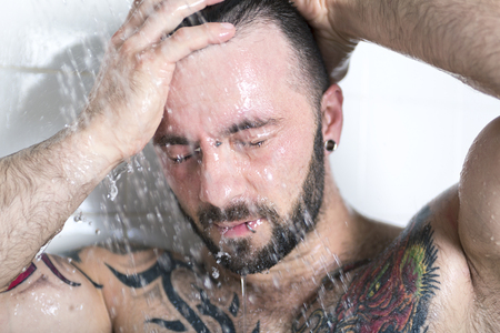 nudist: A sexy man with tattoo on the shower
