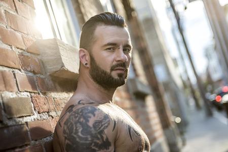 sin camisa: Un hombre atractivo con el exterior tatuaje en una calle de la ciudad Foto de archivo
