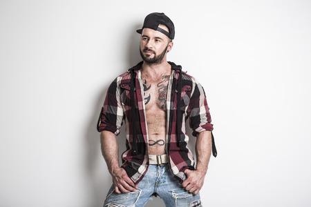 Een sexy man met tatoeage in de voorkant van een grijze achtergrond Stockfoto