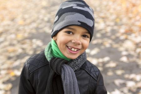 A cute boy with autumn leaves in the park Foto de archivo
