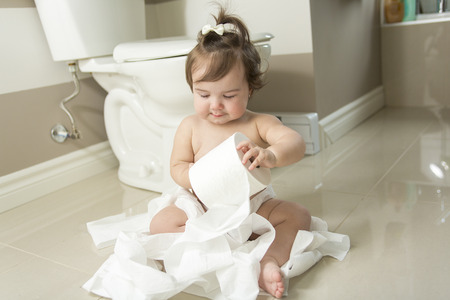 mess: A Toddler ripping up toilet paper in bathroom Stock Photo