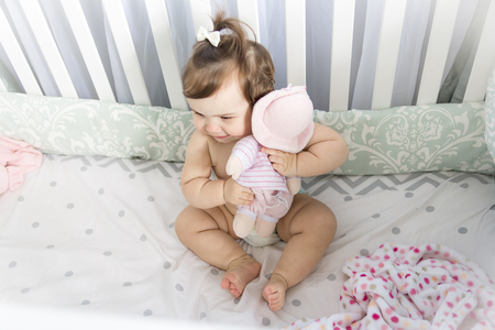 felicity: An Infant baby resting and playing in his little baby bed Stock Photo