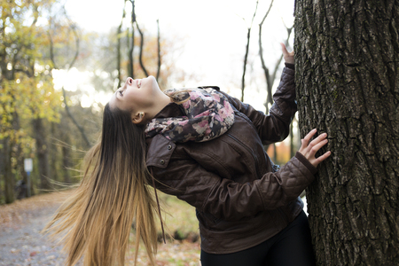 16s: A Portrait of beautiful young brunette girl in the park at fall.