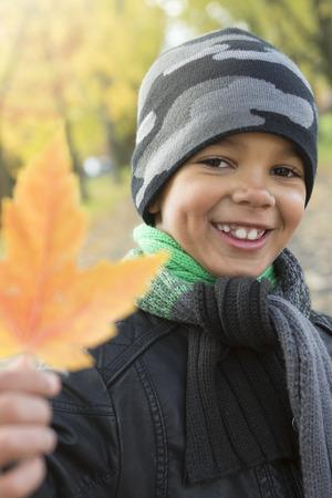 amarillo y negro: Un muchacho lindo con las hojas de otoño en el parque