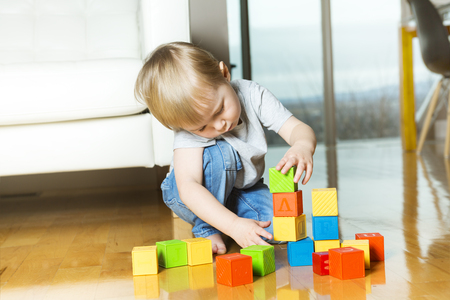 A kid playing toy blocks inside his house