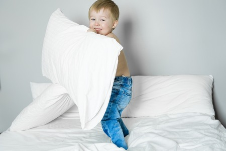 barefooted: A Healthy Lifestyle of young little children boy on bed Stock Photo