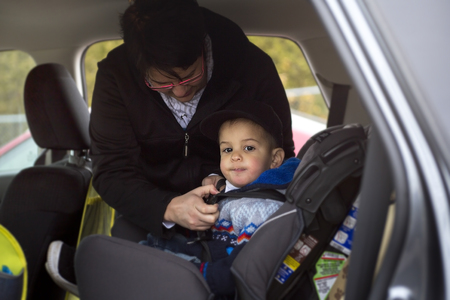 child seat: A Mother in a car having her boy in a child seat