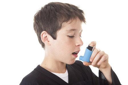 asthma: A teen having an asthma problem  in studio white Stock Photo