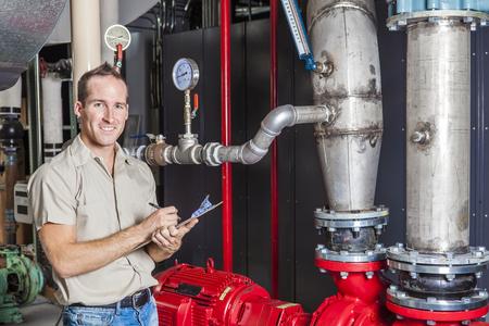 Een technicus inspecteren verwarmingssysteem in de stookruimte Stockfoto