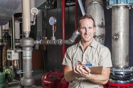 plant: A Technician inspecting heating system in boiler room Stock Photo