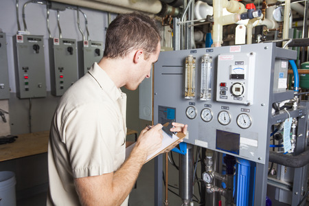 A Technician inspecting heating system in boiler room Stockfoto