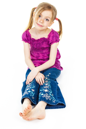 clothe: A beautiful girl child wearing a pink clothe and sit on the floor over a white background. Stock Photo