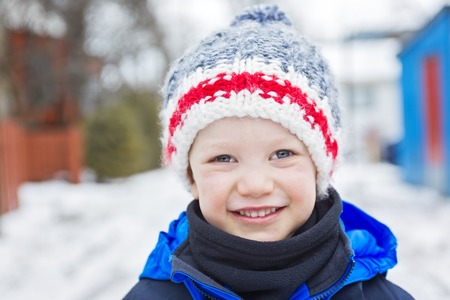warmly: A young boy outside in cold snow winter, dressed warmly and smiling Stock Photo