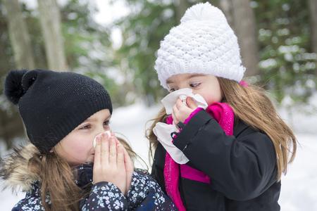 Twee Childs met weefsel buiten in het bos winterseizoen