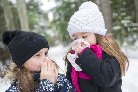 Two childs with tissue outside in forest winter season