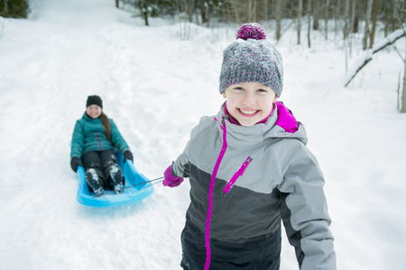 6 7 year old: Two Children Pulling Sledge Through Snowy Landscape